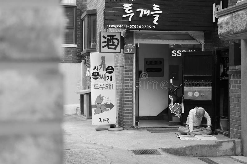Old man reading. In Seoul`s street Dans les rues de Séoul stock images