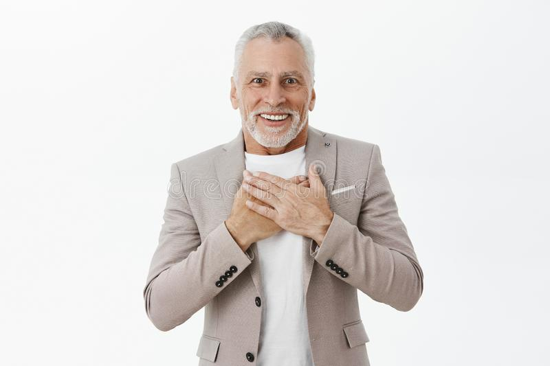Old man receiving heartwarming and touching gift pleased and delighted smiling with crooked teeth at camera holding stock image