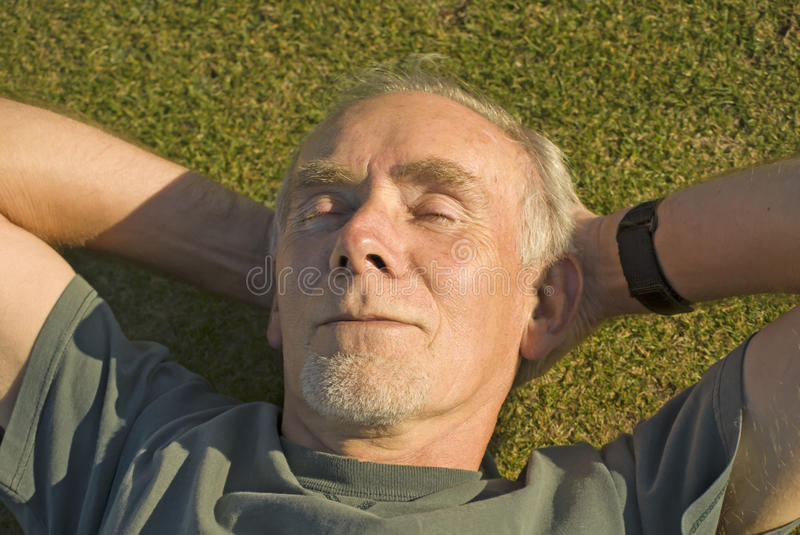 Old man relaxing in the sun on grass stock photography