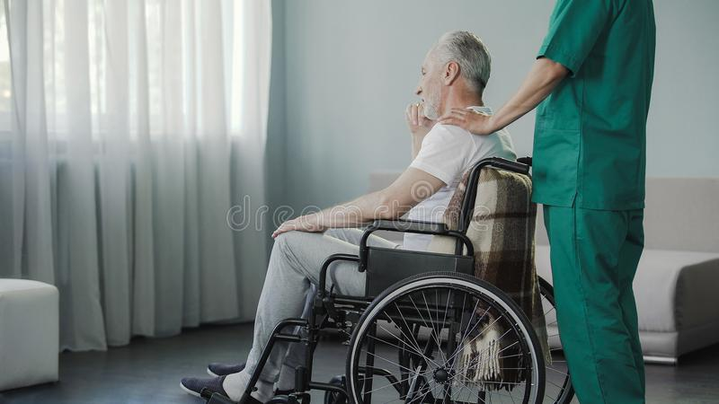 Old man residing on recovery at medical center after serious spine injury stock image