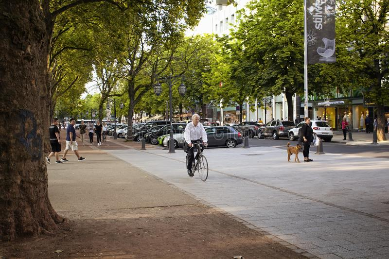 Old man ride bicycle by Konigsallee stock photography
