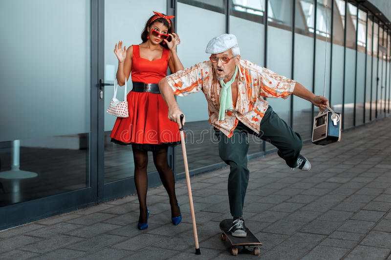Old man ridiculously rides a skateboard. Old men ridiculously rides a skateboard, the women has opened a mouth from surprise stock photos