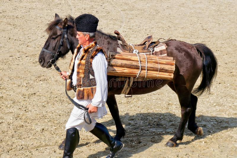 Old man in traditional costume with burden horse stock photo