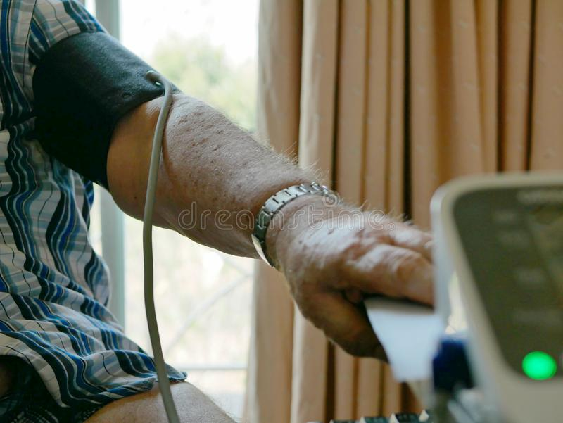 An old man`s arm with a pressure cuff on checking his blood pressure at home by himself royalty free stock images