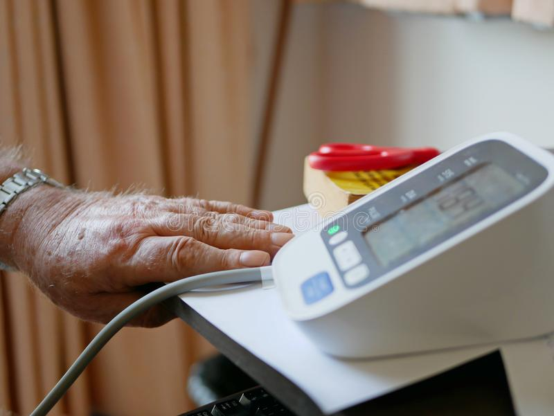 An old man`s hand placed next to the monitor checking his blood pressure at home by himself stock images