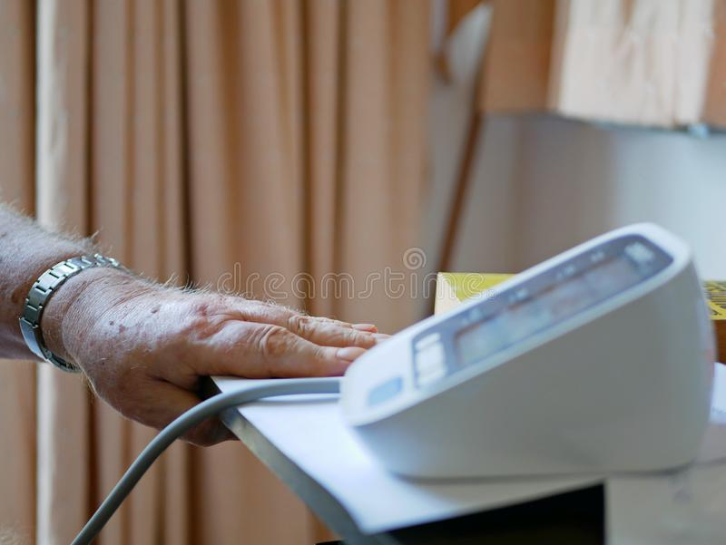 An old man`s hand placed next to the monitor checking his blood pressure at home by himself royalty free stock image