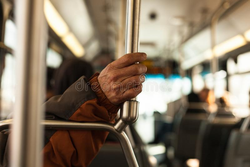 The old man`s hand is seen holding the iron handle to protect himself while the bus is running royalty free stock photos