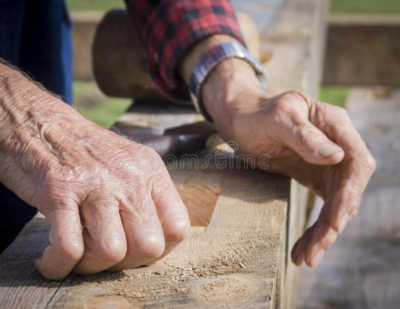 An Old Man's Hands Resting on a Wood Timber. Wrinkled hands of an old man resting on a large wooden timber beam stock photography