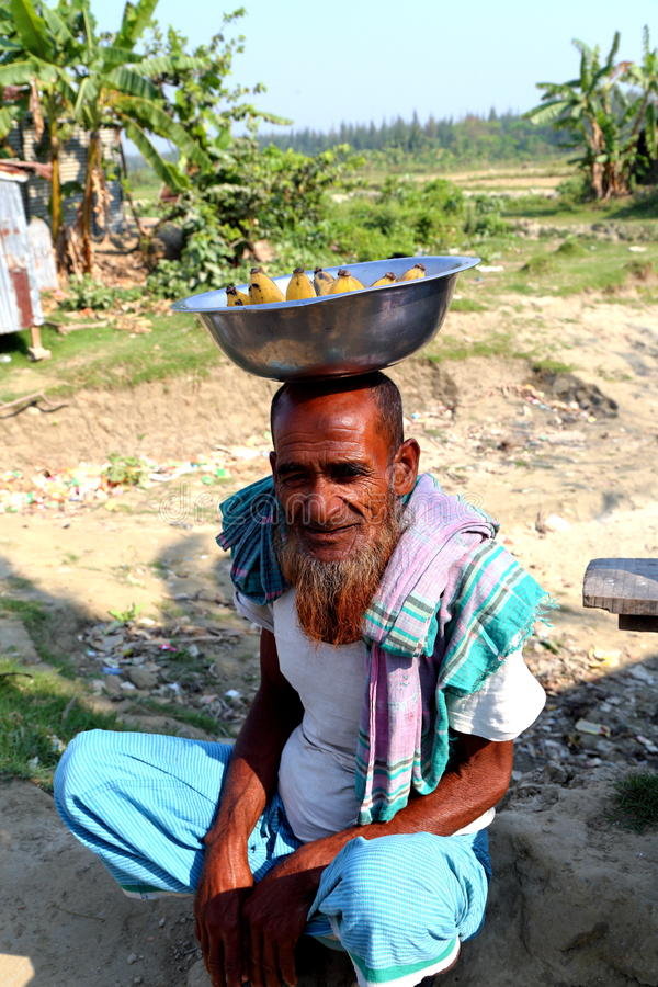 Old man is sitting with banana. Old man is doing small banana business to the people who go to Nijhum Dwip at Hatiya upazila. It is situated in Noakhali District stock photos