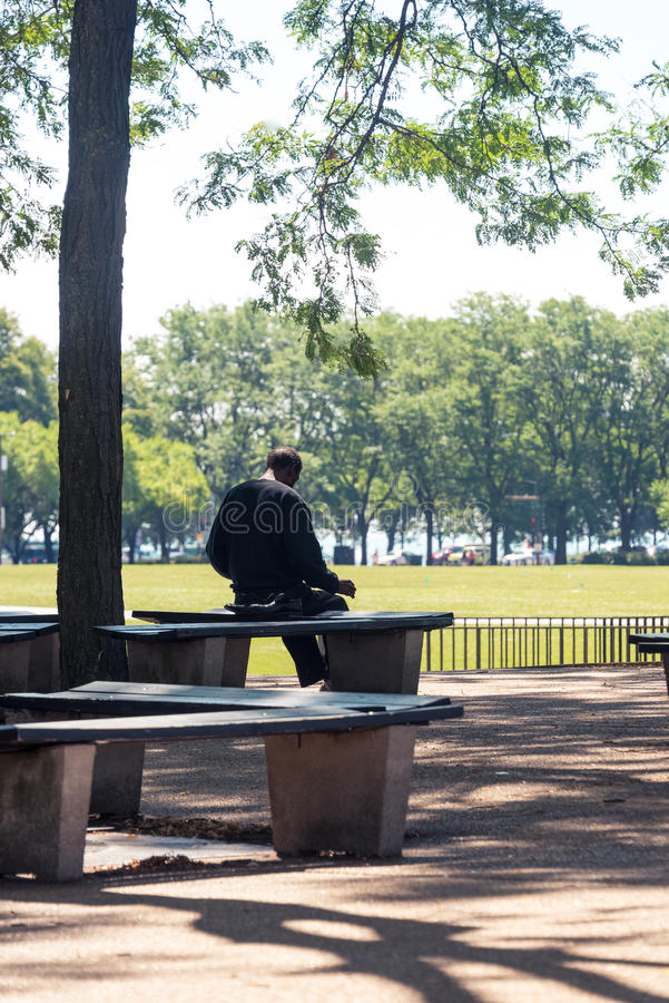 Old man sitting on a bench in a Chicago park royalty free stock images
