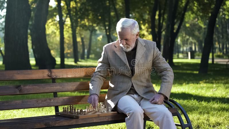 Old man sitting on bench in park alone and playing chess, retirement benefits. Stock photo stock photography