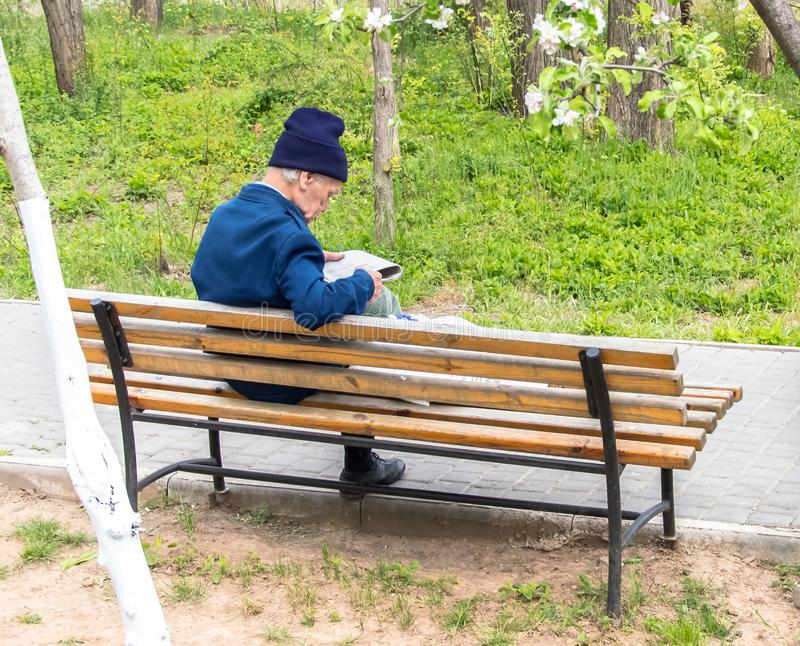 An old man is sitting on a bench stock photography