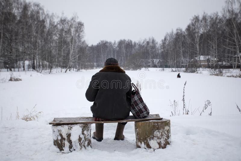 Old man sitting on a bench in the winter, the view from the back. Old man sits on a bench in the winter in front of a frozen pond with fishermen, the view from royalty free stock images