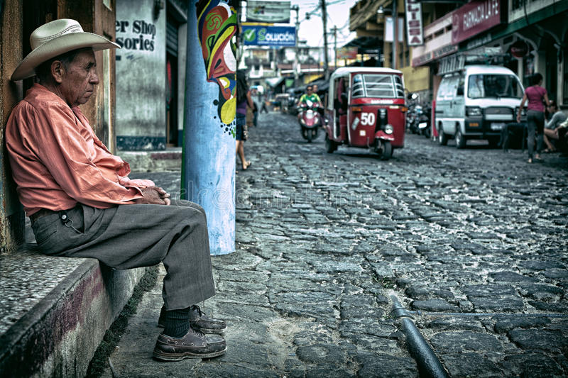 Old Man sitting on an old cobblestone street with traffic driving by royalty free stock photos
