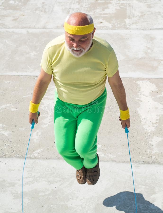 Old man skipping rope. Fitness senior man skipping with a jump rope outdoors. Old man skipping rope. Fitness senior man skipping with a jump rope outdoors royalty free stock photos