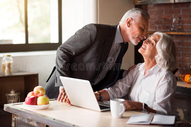 Old man in smart suit kissing his wife good-bye stock photos