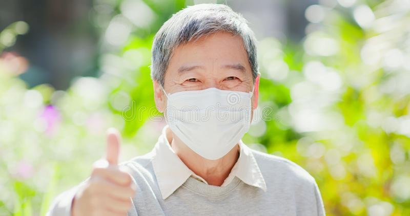 Old man thumbup with mask royalty free stock photos