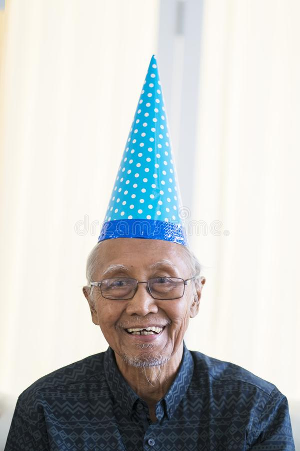 Old man smiling at camera with birthday hat. Portrait of old man smiling at the camera while wearing birthday hat at home royalty free stock photo