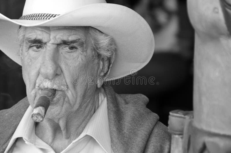 Old man smoke a cigar royalty free stock photos