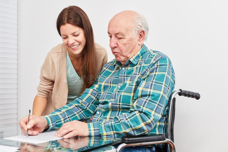 Old man solves puzzles as a prevention against dementia. Old men solves puzzles and trains his memory as a prevention against dementia royalty free stock image
