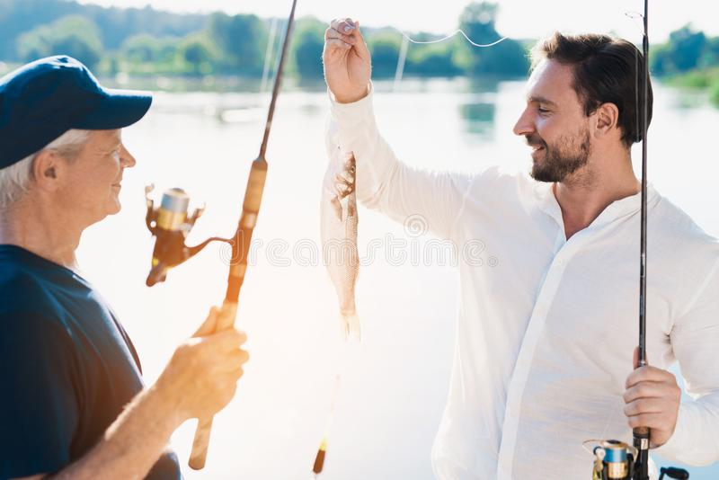 An old man with a spinning stands in front of a man who shows him the fish he just caught royalty free stock photography