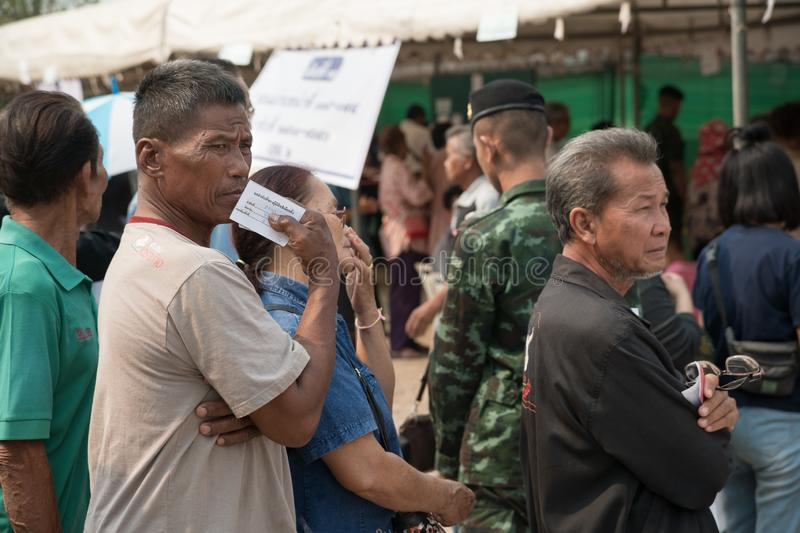 Old man stands in row for Pre-election at Khonkaen, Thailand. Khonkaen, Thailand - March 17, 2019: Old man with queue number ticket in hand stands in row for Pre stock photos