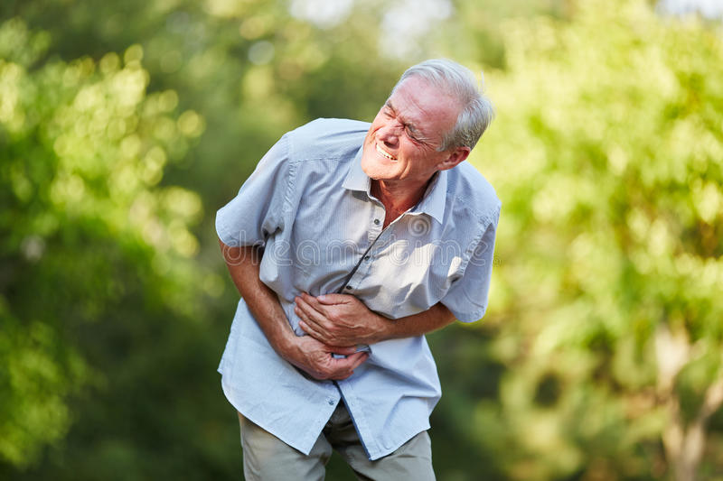 Old man with stomach ache. Toching his stomach in the nature stock image