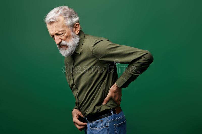Old man suffering from referred pain in the back. Weakness concept. shooting, piercing pain in back. close up side view photo royalty free stock photos