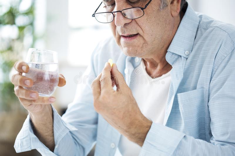 Old man taking a pill stock photos