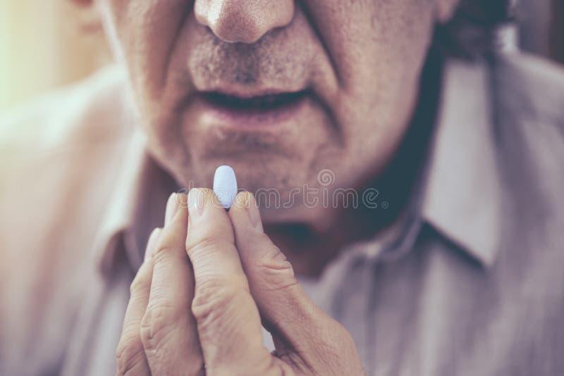 Old man taking a pill. Old man taking a  pill royalty free stock photos
