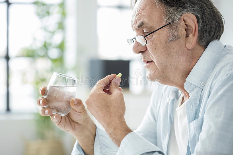 Old man taking a pill royalty free stock photo