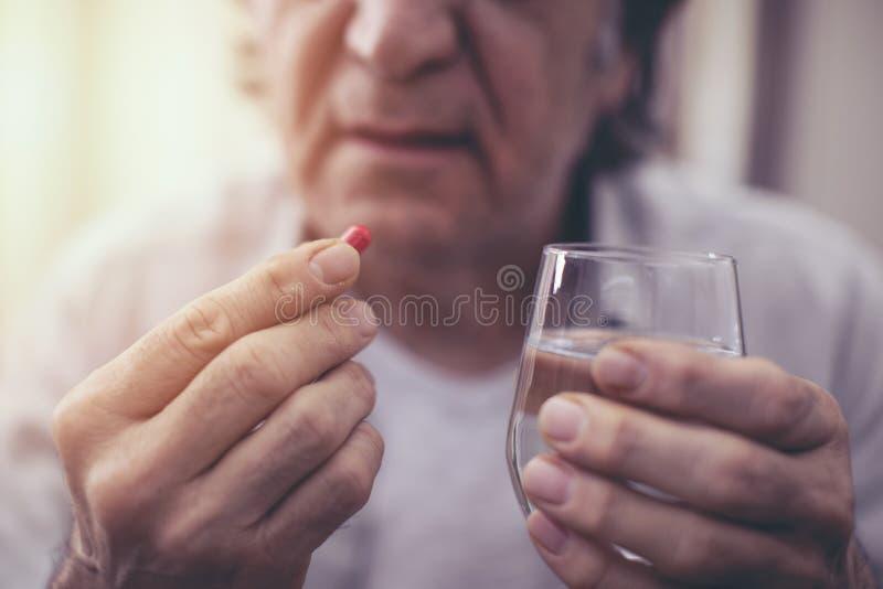 Old man taking a pill. Old man taking a  pill royalty free stock image