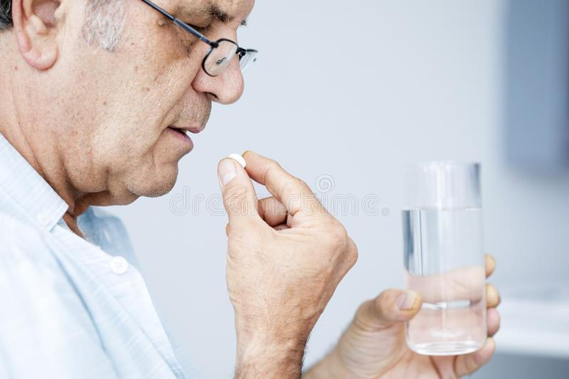 Old man taking pills. In home royalty free stock images