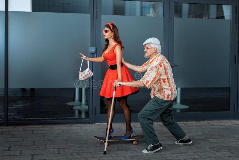 Old man teaches to ride a skateboard young girl. royalty free stock photos
