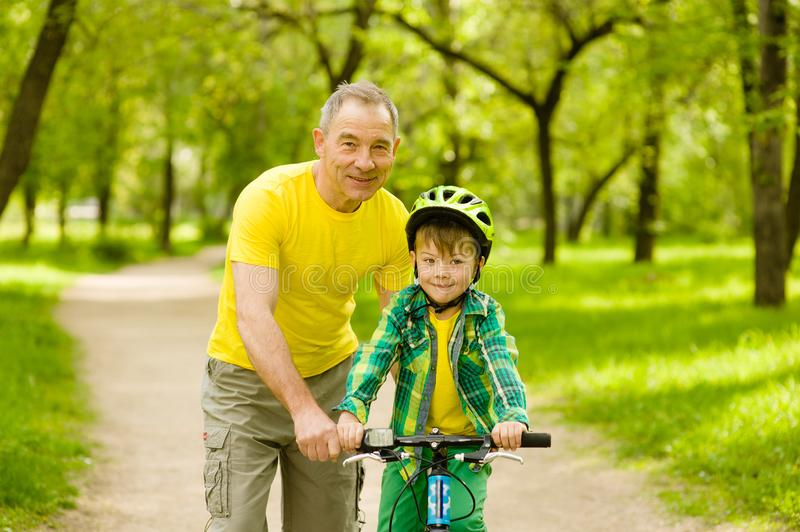 An old man teaching his grandson to ride a bike royalty free stock photography