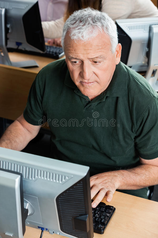 Old Man Using Computer In Classroom stock photography