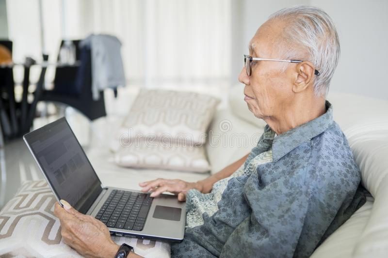 Old man using laptop computer on the sofa stock image