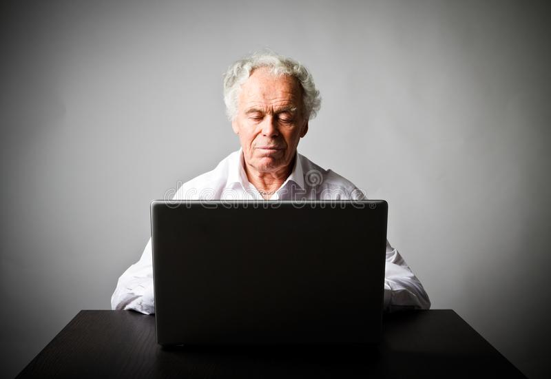 Old man using a laptop royalty free stock photo
