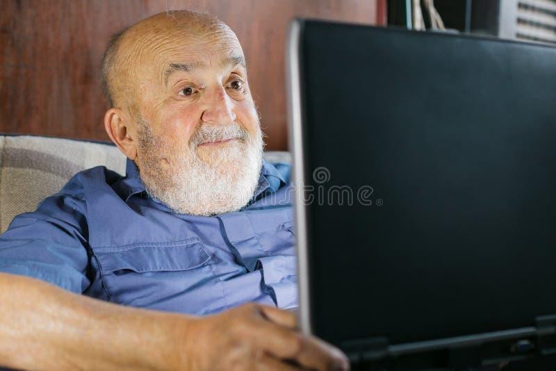 old man using laptop stock photo