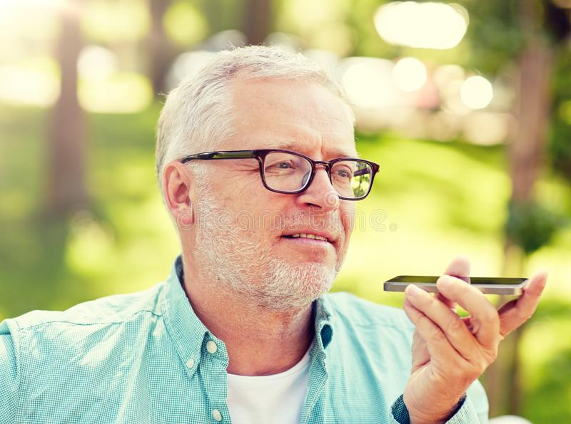 Old man using voice command recorder on smartphone. Technology, senior people, lifestyle and communication concept - close up of happy old man using voice royalty free stock images