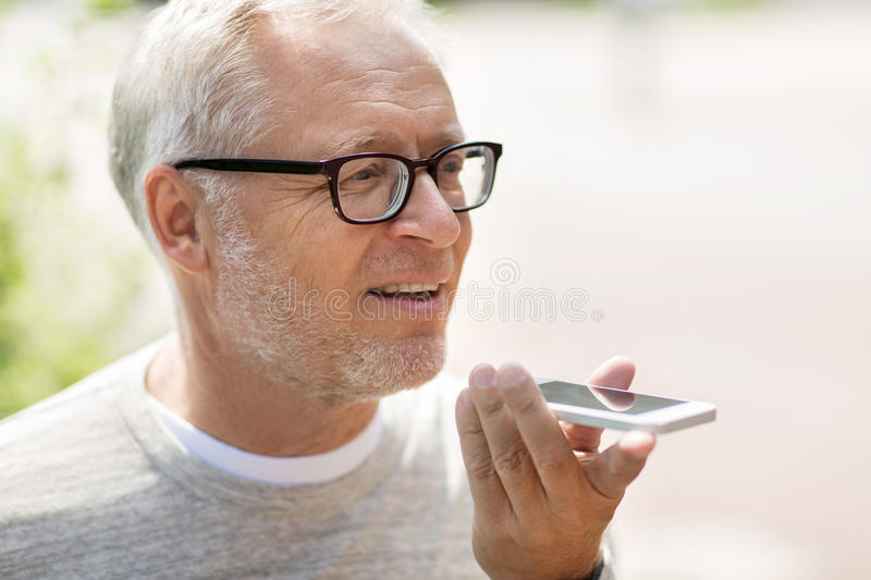 Old man using voice command recorder on smartphone. Technology, senior people, lifestyle and communication concept - close up of happy old man using voice royalty free stock photos