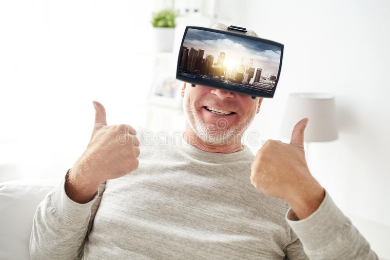 Old man in virtual reality headset shows thumbs up. Technology, augmented reality, gaming, entertainment and people concept - senior man with singapore city on stock images