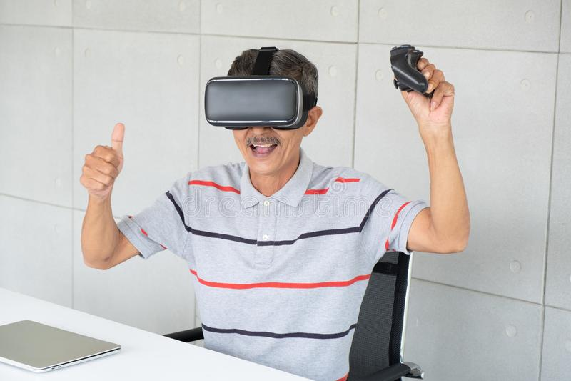 Old man in vr reality glasses of virtual reality with  playing game royalty free stock photos