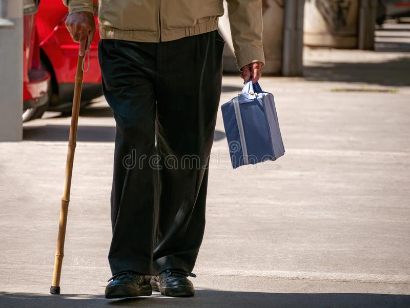 Old man walk with small suitcase and stick royalty free stock images