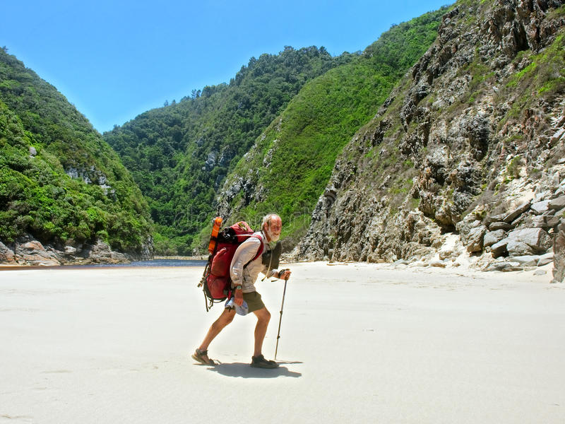 Old man walks on beach with a backpack stock photos