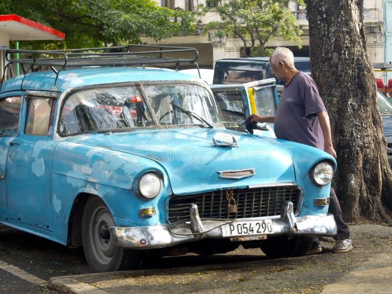 Old man washing his vintage car in Havana. stock image