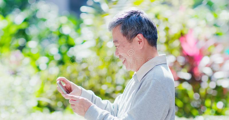 Old man watch video. By smart phone outdoor royalty free stock photography