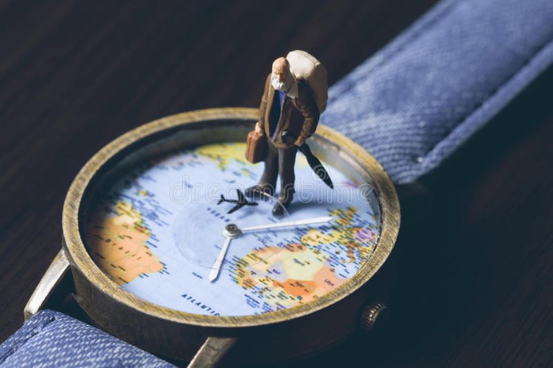 Old man on watches with world map, vintage toned photo. World travel banner. Senior traveler figurine. World time zones. Travelling around world concept stock photo