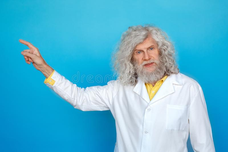 Old man wearing doctor`s gown studio isolated on blue standing pointing aside explaining topic stock images