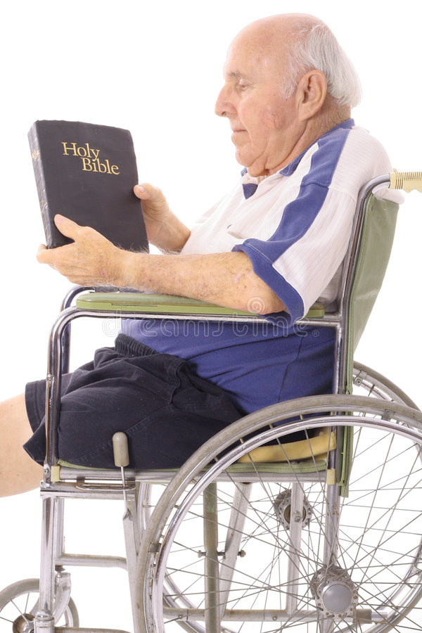 Old man in wheelchair reading a bible. Isolated on white stock image